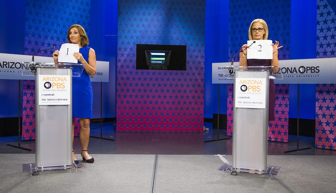 Rep. Martha McSally (left) and Rep. Kyrsten Sinema hold up papers indicating who will receive the first question in the debate at the Arizona PBS studios at the Walter Cronkite School of Journalism and Mass Communication at Arizona State University in Phoenix on Oct. 15, 2018.