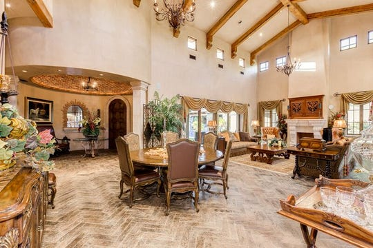 The two-story Tuscan estate has architectural design features that include double barrel vaulted ceilings with brick and stone treatments, handcrafted vigas and custom herringbone patterned tile work