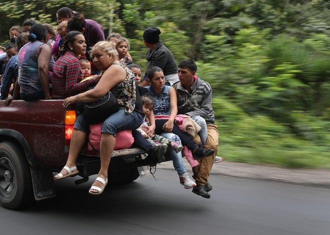 Varios migrantes hondureños viajan sentados en la caja de una camioneta.