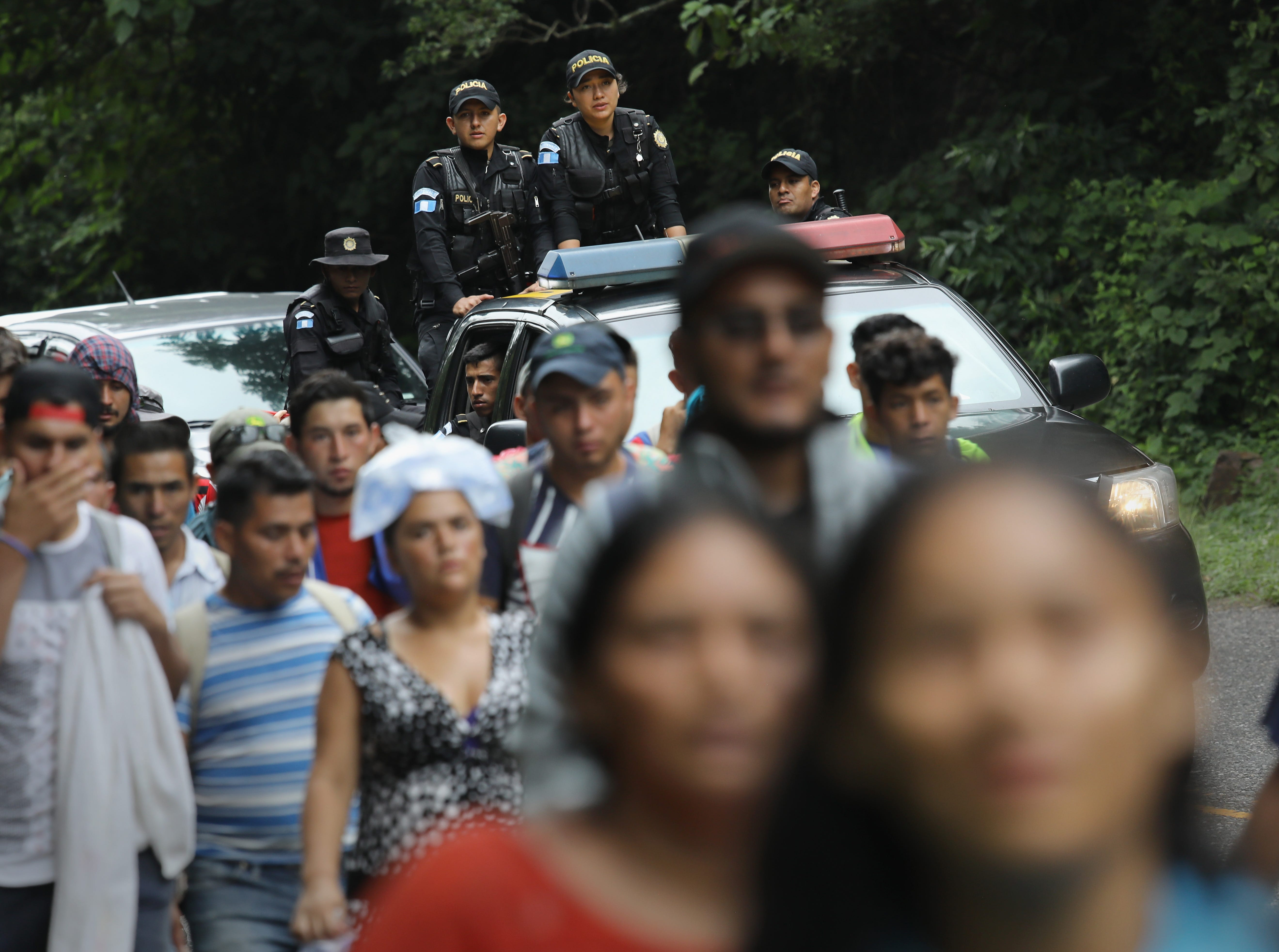 QUEZALTEPEQUE, GUATEMALA - OCTOBER 16:  As Guatemalan police look on, Honduran immigrants, some of more than 1,500 people traveling in a migrant caravan, walk north on October 16, 2018 near Quezaltepeque, Guatemala. A caravan of Central Americans, the second of its kind in 2018, began in San Pedro Sula, Honduras with plans to march north through Guatemala and Mexico in route to the United States. Honduras has some of the highest crime and poverty rates in Latin America. (Photo by John Moore/Getty Images)