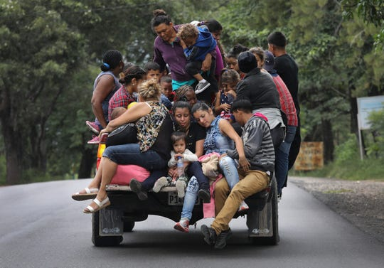 Honduran immigrants, some of more than 1,500 people in a migrant caravan, travel north on Oct. 16 near Quezaltepeque, Guatemala.