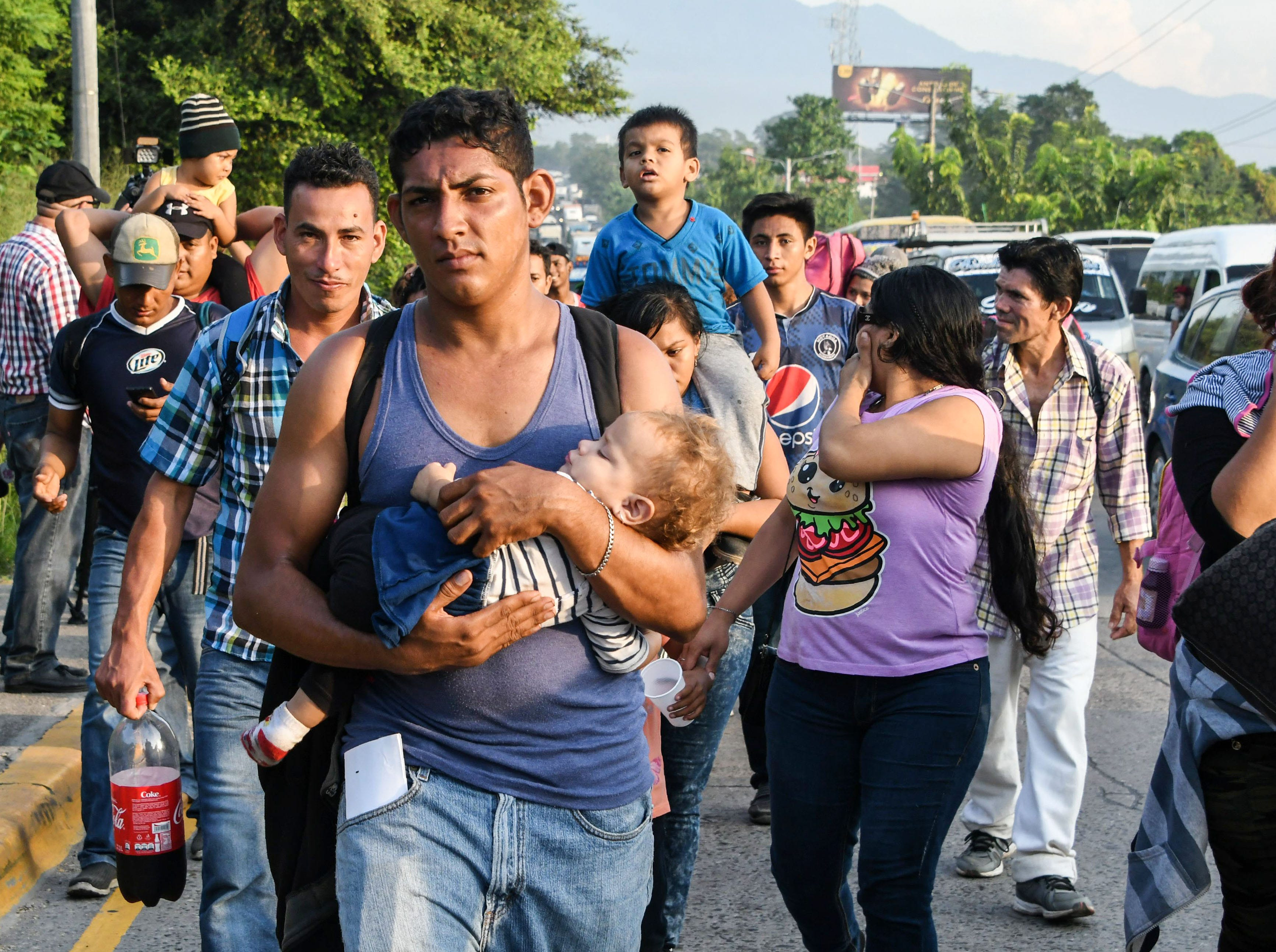 An Honduran man carries a child on is arms  during an exodus towards the US from San Pedro Sula, 180 kms north from Tegucigalpa, on October 13, 2018. - Hondurans decided to left their country due to insecurity and the lack of employment opportunities. The exodus started from the bus station in San Pedro Sula towards the border with Guatemala. (Photo by ORLANDO SIERRA / AFP)        (Photo credit should read ORLANDO SIERRA/AFP/Getty Images)