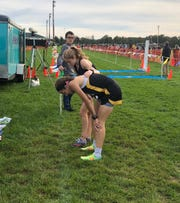 Dallastown's Emily Schuler puts her arm around Red Lion's Kiersten Lloyd after the York-Adams League Girls' Cross Country Championship Run at Gettysburg. Schuler finished first and Lloyd was second.
