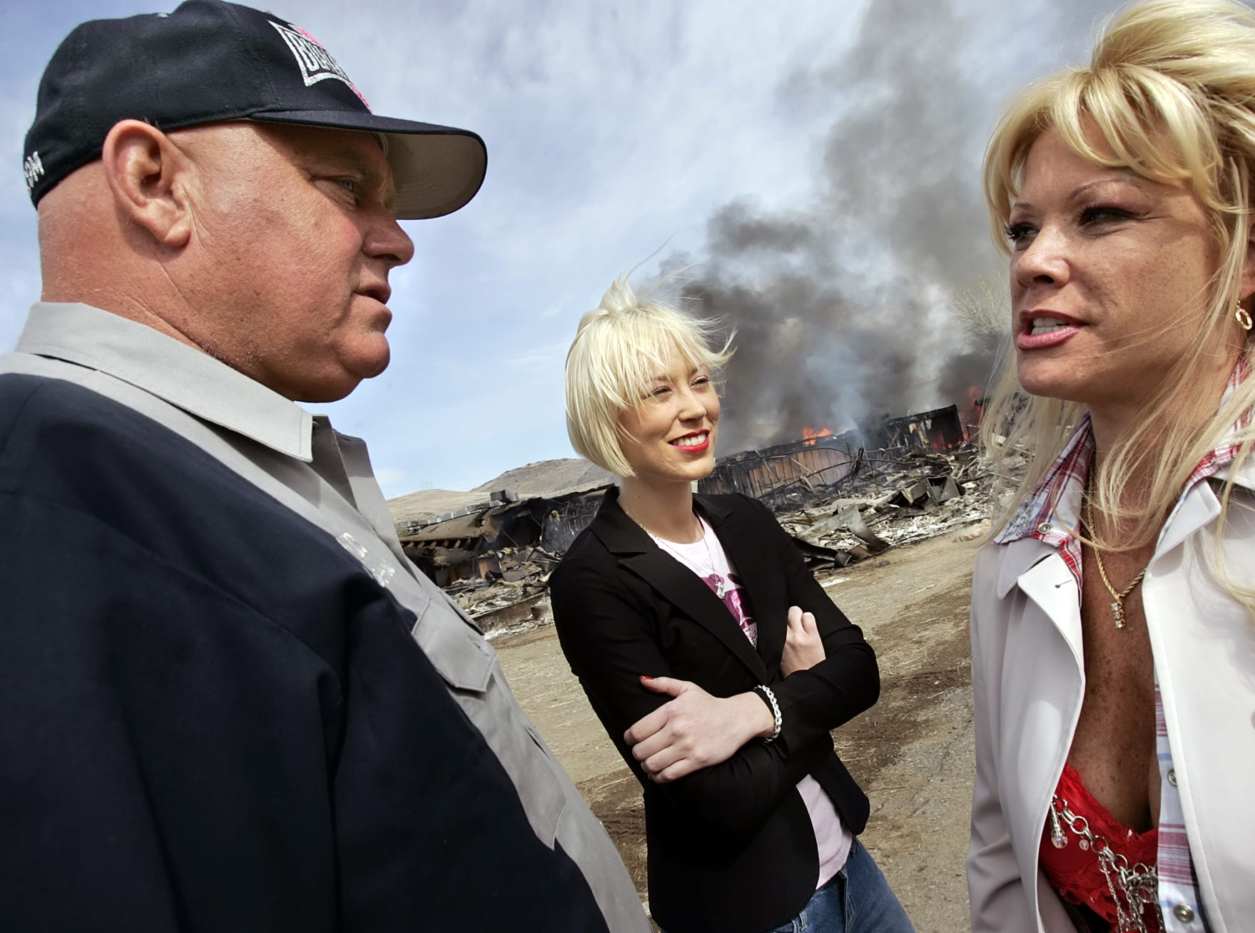 """Moonlite Bunny ranch brothel owner Dennis Hof, left, talks with two of his employees, Brooke Taylor, center, and a woman who identified herself as """"Airforce Amy"""" as the remains of the former Mustang Ranch 2 brothel burns during a training exercise, east of Reno, Nev., Sunday, March 25, 2007. Hof donated the structure to the Storey County fire department for fire training. (AP Photo/Nevada Appeal, Chad Lundquist)"""