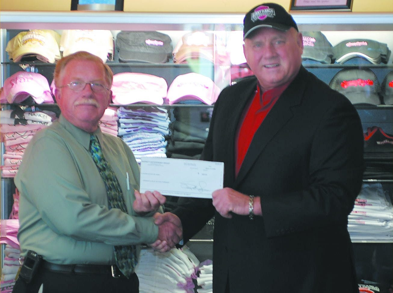 Photo courtesy BunnyRanch  Dalos Graf, President of Kiwanis Club of Dayton Township, accepts a check from Dennis Hof of The BunnyRanch for $500. Employees at the BunnyRanch raised the money to assist the service club to achieve its fund-raising goal of providing scholarships to at least four graduating seniors from the area.