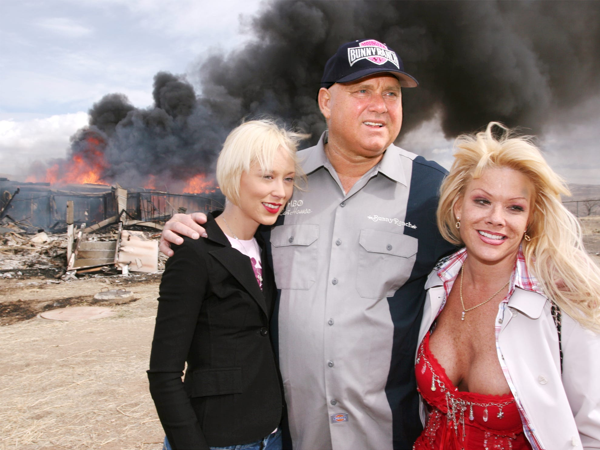 """Moonlite Bunnyranch brothel owner Dennis Hof poses with two of his """"working girls"""" Brooke Taylor, left, and a woman working under the name """"Airforce Amy"""", right, as firefighters burn down remains of the former Mustang Ranch 2 brothel east of Reno, Nevada on Sunday, March 25, 2007. Hof donated the building to the Storey County fire department for fire training. (AP Photo/Debra Reid)"""