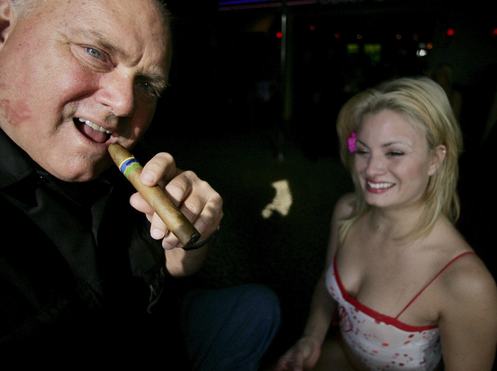 Moonlite BunnyRanch owner Dennis Hof smokes a cigar at his brothel's entrance, Thursday, April 7, 2005, in Mound House, Nev. At right is  Sierra, a prostitute at the brothel. Although county governments collect license fees, the state of Nevada has never  taxed brothels . If an industry lobbying group and an anti-prostitution lawmaker have their way, that could change this year. (AP Photo/Brad Horn)