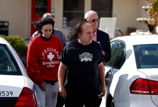 Ron Jeremy, front right, and Heidi Fleiss, left, walk out of the Love Ranch brothel, Tuesday, Oct. 16, 2018, in Pahrump, Nev. Dennis Hof, a pimp who gained notoriety for his Nevada brothels, was found dead hours after his 72nd birthday bash, authorities said Tuesday. Hof had said his party would be attended by porn star Jeremy. It wasn't immediately clear Tuesday if Jeremy attended.