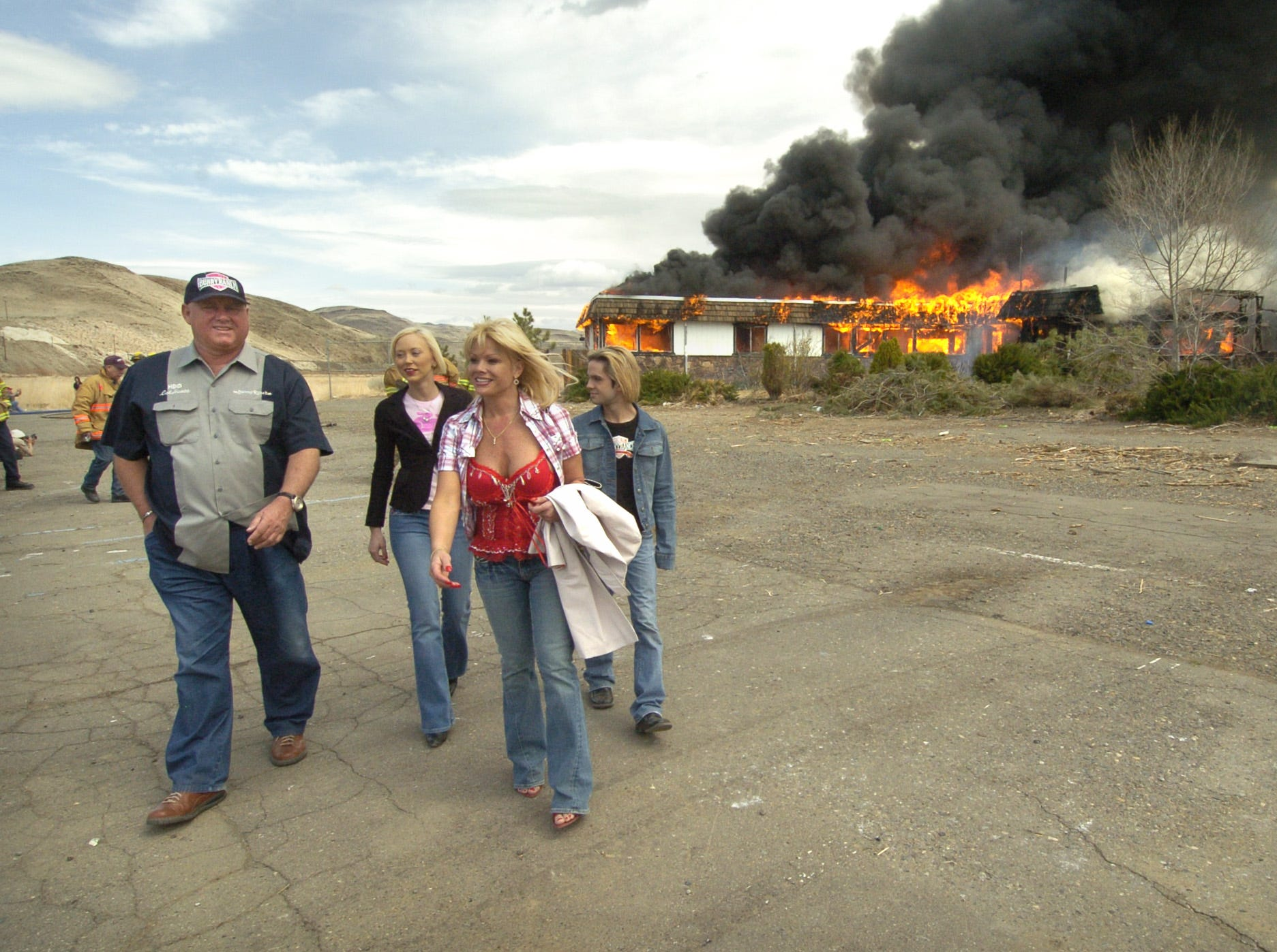 Moonlite Bunny Ranch owner Dennis Hof, left, walks from the scene as the old Mustang 2 brothel building goes up in flames Sunday, March 25, 2007. Hof, the owner of the building, donated it to Storey County so firefighters could use it for traning purposes. With Hof are Bunny Ranch working girls Brooke Taylor and Air Force Amy, along with bartender/personal assistant Kristopher Mendibil. Photo by David B. Parker.