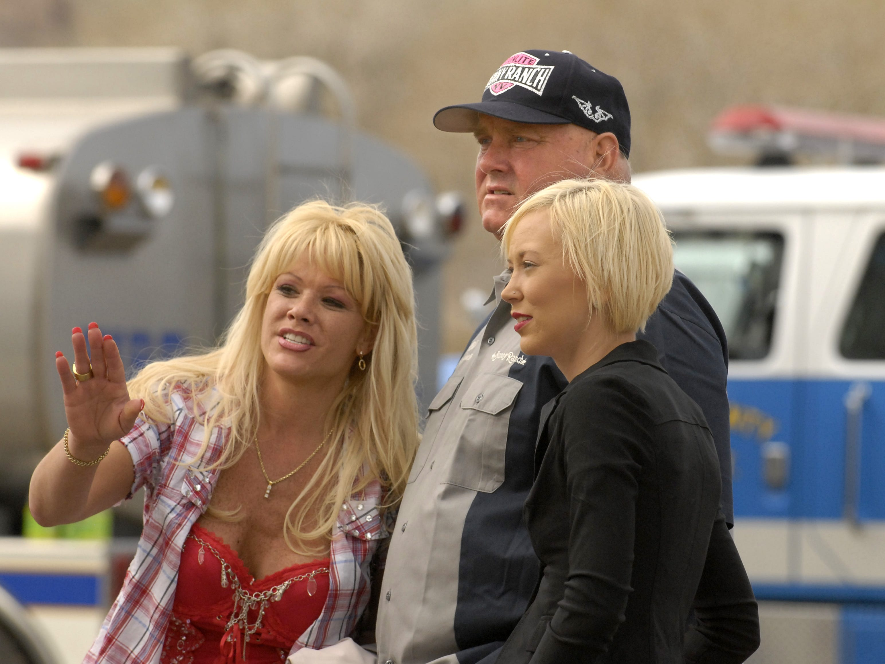Air Force Amy, left, Dennis Hof and Brooke Taylor of the Moonlite Bunny Ranch watch as the old Mustang Ranch 2 building goes up in flames during a training burn Sunday, March 25, 2007. Amy used to work in the building before it closed in 1999. Photo by David B. Parker.