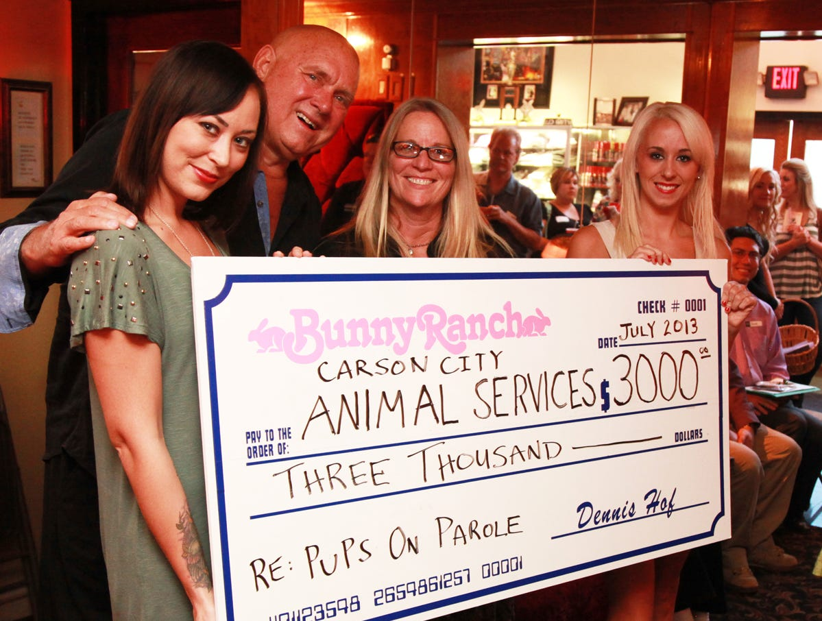 Owner Dennis Hof of The BunnyRanch in Mound House (second from left) is joined by employees Brooke Taylor (left) and Krissy Summers (right) to present a $3,000 donation check to Tonya Petri (second from right) of Carson City Animal Services for its Pups on Parole Program. The presentation was made during the Dayton Chamber of Commerce Mixer on July 18 at The Bunny Ranch, which each year collects donations to a charitable local non-profit organization. Through the Pups on Parole program, at-risk dogs are rescued from a shelter and trained as companion pets.