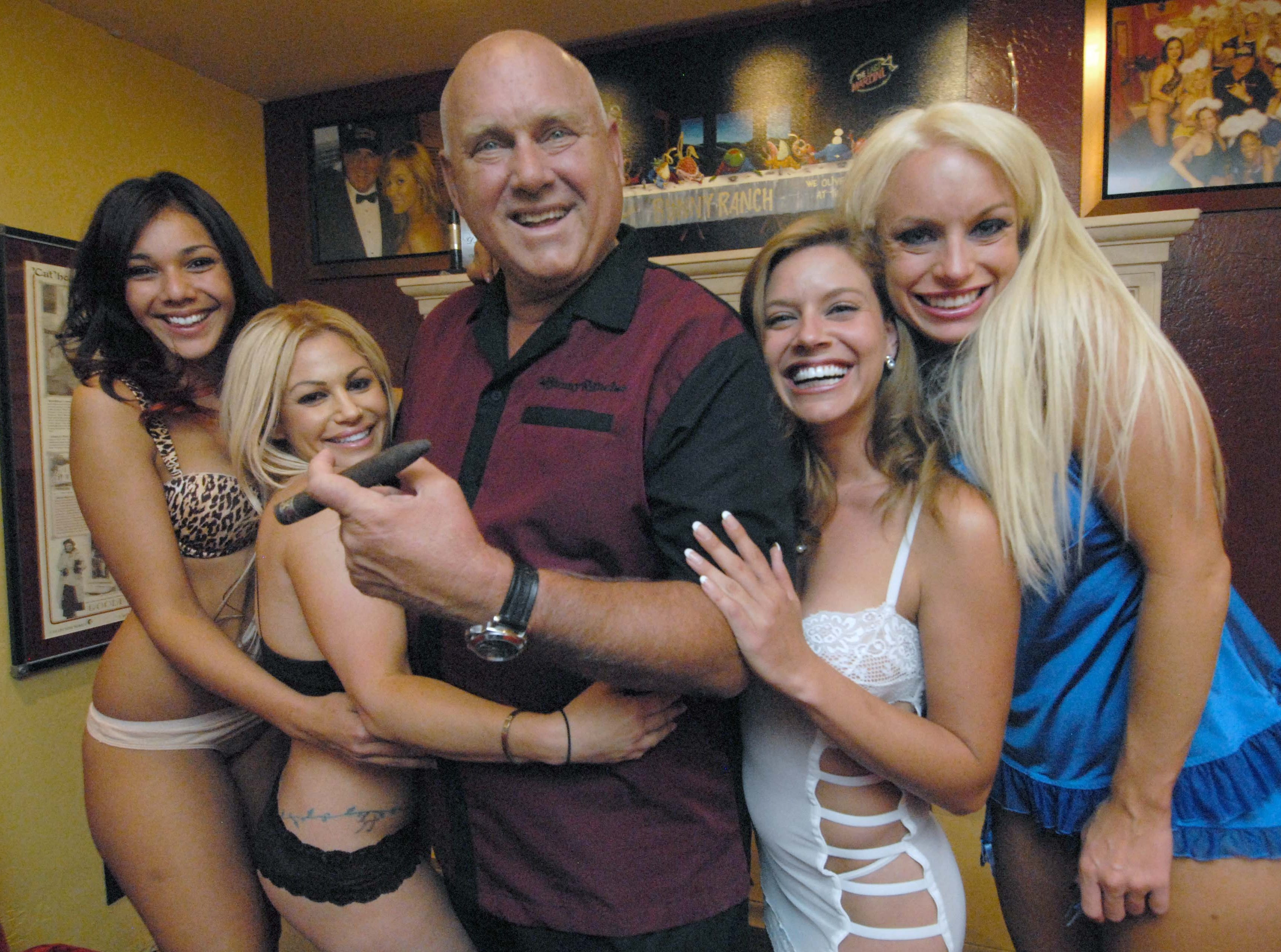"""Published caption: LISA J. TOLDA/RENO GAZETTE-JOURNAL Owner Dennis Hof, with some of the women at the Moonlite Bunny Ranch, said business has slowed at the Mound House brothel because of higher fuel prices.  ooo  Owner Dennis Hof poses Thursday June 27, 2008 with some of his """"working girls"""" in the parlor of his Moonlite BunnyRanch in Mound House, east of Carson City."""