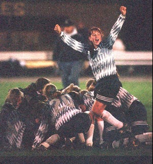 Mercy's Trish Raniewicz and her teammates mob Abby Wambach who scored the tying and winning goals to beat Penfield in overtime, 3-2, in the Section V Class A semifinals on Nov. 1, 1995.