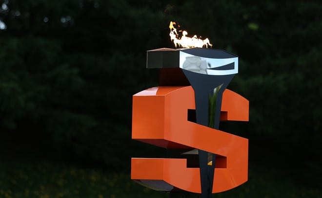 The Olympic torch burns bright at the football stadium during a recent commencement ceremony.