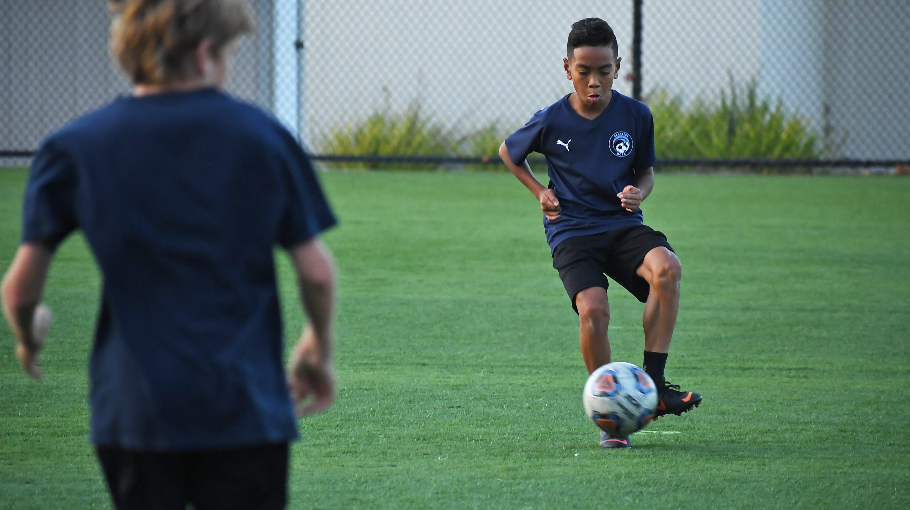 Sekou Mathews (right) has played soccer since age three and excels on the pitch. The 12-year-old recently garnered attention from FC Barcelona, one of the most popular clubs in the world.
