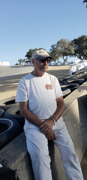 In this photo, Richard Reins sits on a racetrack barrier.