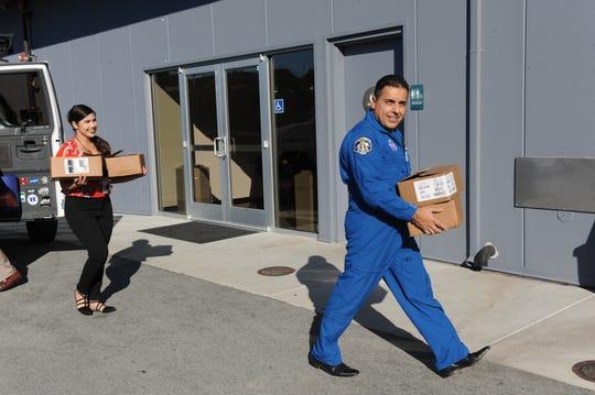 José Hernández, derecha, entrega copias de sus libros antes del 24.° evento anual Words and Wine de la Fundación para las Bibliotecas Gratuitas del Condado de Monterey.