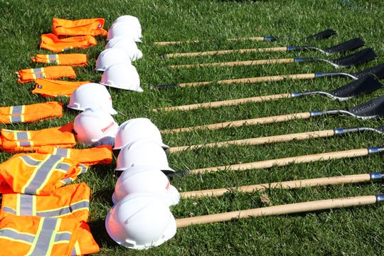 Vests, hats and shovels are laid out on the ground at the groundbreaking of the Mt. Toro High School multipurpose center.