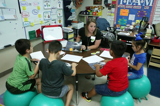 A teacher at Lamar Elementary works with a group of students in small guided reading instruction Oct. 3, 2018, while the rest of her class is separated into work stations.