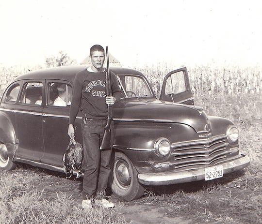 Roger Wiltz poses during pheasant season outside his 1948 Plymouth.