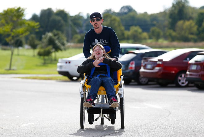 Twelve-year-old Claire Dula rides on a tandem adaptive bike with Cyrus Taylor, a community recreation supervisor with the Springfield-Greene County Park Board, at Rutledge-Wilson Farm Park on Tuesday, Oct. 16, 2018.