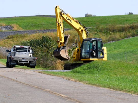 An excavator makes its way back up the hill from the site of the Kerch family cemetery, located on the ground of Shenandoah Valley Regional Airport, after an archeological investigation at the site on Tuesday, Oct. 16, 2018.