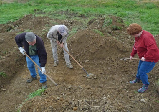 Volunteers (from left to right) Clarence Allen, Dr. Dennis Blanton, and Kate Delaney carefully remove the soil from test strips of land next to the historic Kersh Cemetery. The three were part of a collaboration between the airport, the historical society, and interested community members working to document, restore, and protect the cemetery.