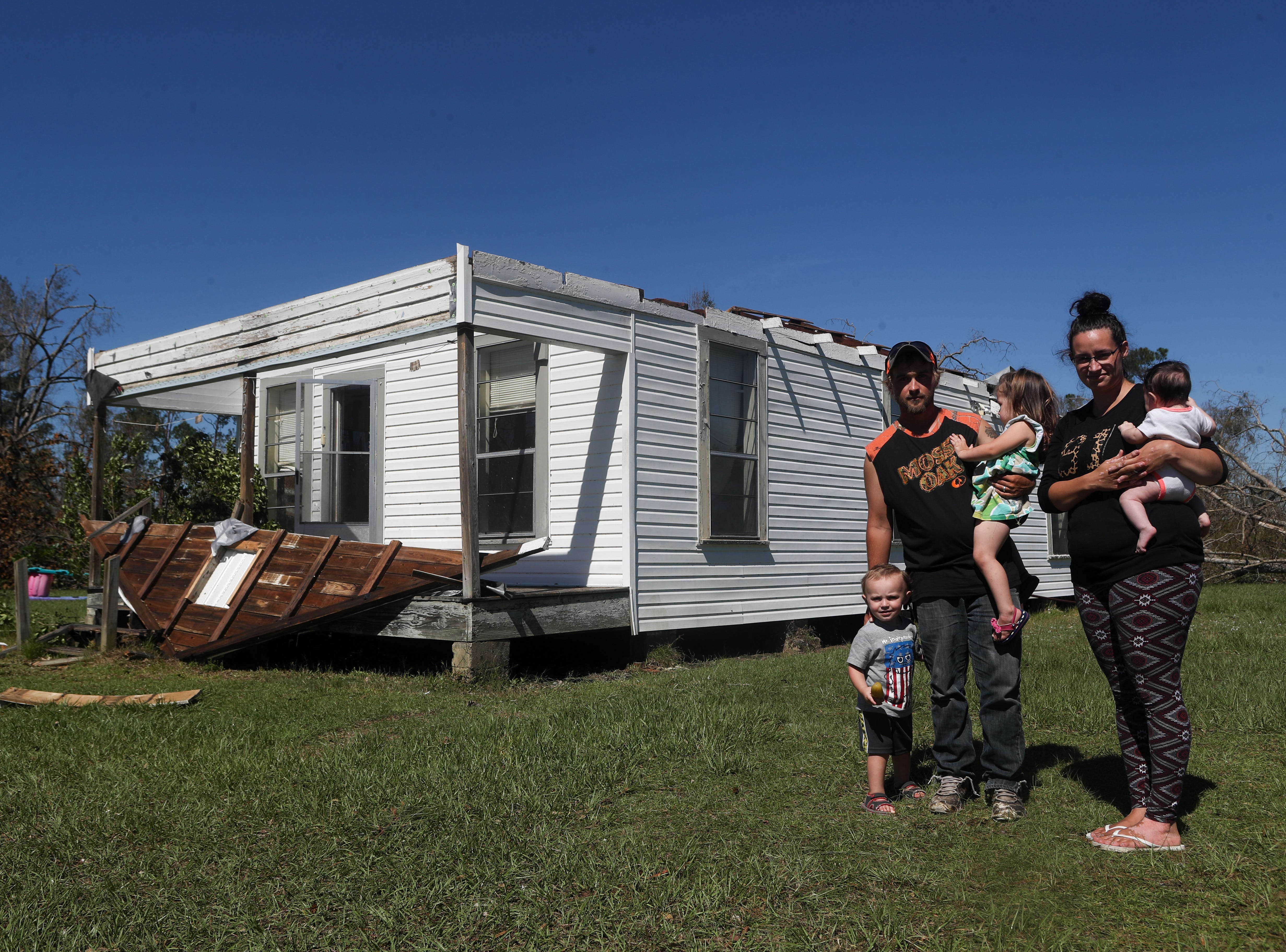 Caleb Hoffman and his family in front of their home in the aftermath of Hurricane Michael Friday, Oct. 12, 2018.