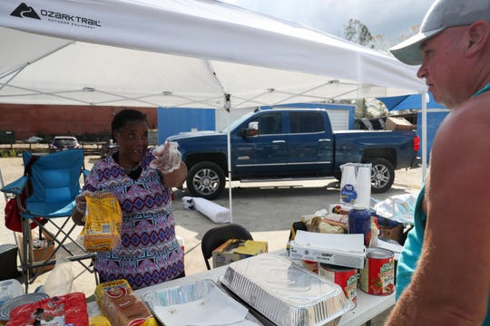 Rhonda Cooper serves food under a tent next to the Dalton Trucking Inc. semi trailer at the corner of Main Street North and Central Avenue West in Blountstown, Fla. in the aftermath of Hurricane Michael Thursday, Oct. 16, 2018.