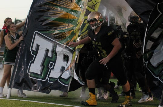 Lincoln offensive lineman Evan Quigley leads his team onto the field as the Lincoln Trojans played host to the Leon Lions at Gene Cox Stadium on Monday, Oct. 15, 2018. The Trojans won 56-21 to capture a District 2-7A title.