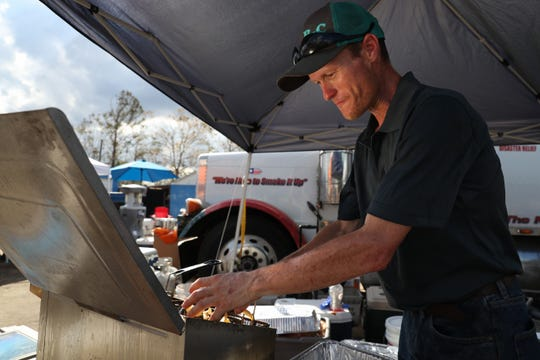 Cole Johnson, a volunteer from Texas, cooks potatoes next to the Dalton Trucking Inc. semi trailer at the corner of Main Street North and Central Avenue West in Blountstown, Fla. in the aftermath of Hurricane Michael Thursday, Oct. 16, 2018.