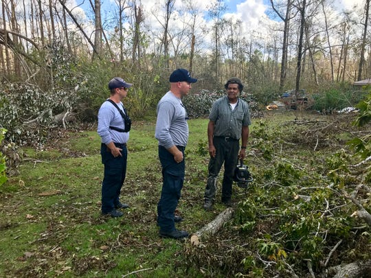 Lt. Garrett Warren, left, and Lt. Mike Coe of Florida Urban Search and Rescue Task Force 7, speak on Tuesday with Harry Capehart, a Grand Ridge resident who rode out Hurricane Michael in his mobile home.