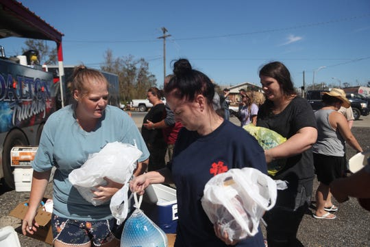 Tanya Savell, Ariel Savell and Erin Blackburn bring turkey and ham for Dalton Trucking Inc. to cook and give out to community members in Blountstown, Fla. in the aftermath of Hurricane Michael Friday, Oct. 12, 2018.