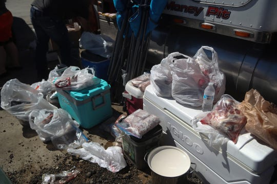 Meat piles up after community members drop it off for Dalton Trucking Inc. to cook and distribute to those in need in Blountstown, Fla. in the aftermath of Hurricane Michael Friday, Oct. 12, 2018.