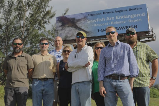 Members of the multi-agency sawfish recovery team pose in front of a billboard on U.S. 1 in Florida City funded by grant money.
