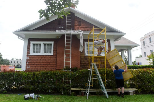 Blaine Stenvik, along with his stepson Anthony Venturini, construct a scaffold to replace and paint cedar shingles as part of a preservation project on the Women's Club building in downtown Vero Beach.