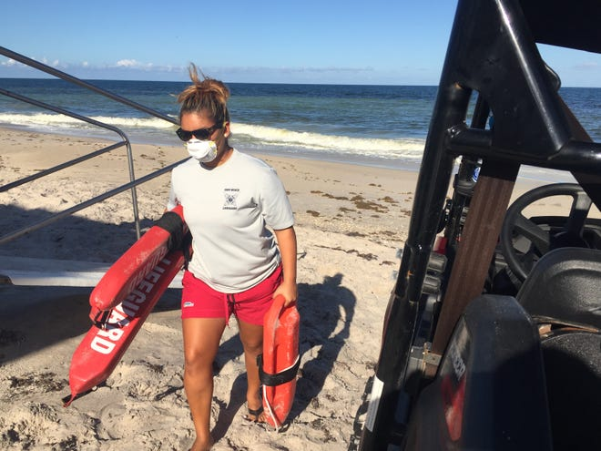 Cierra Flores, a lifeguard stationed between Conn and Jaycee beaches in Vero Beach, wears a mask while putting away gear amid suspected red tide conditions Monday afternoon October 15, 2018.