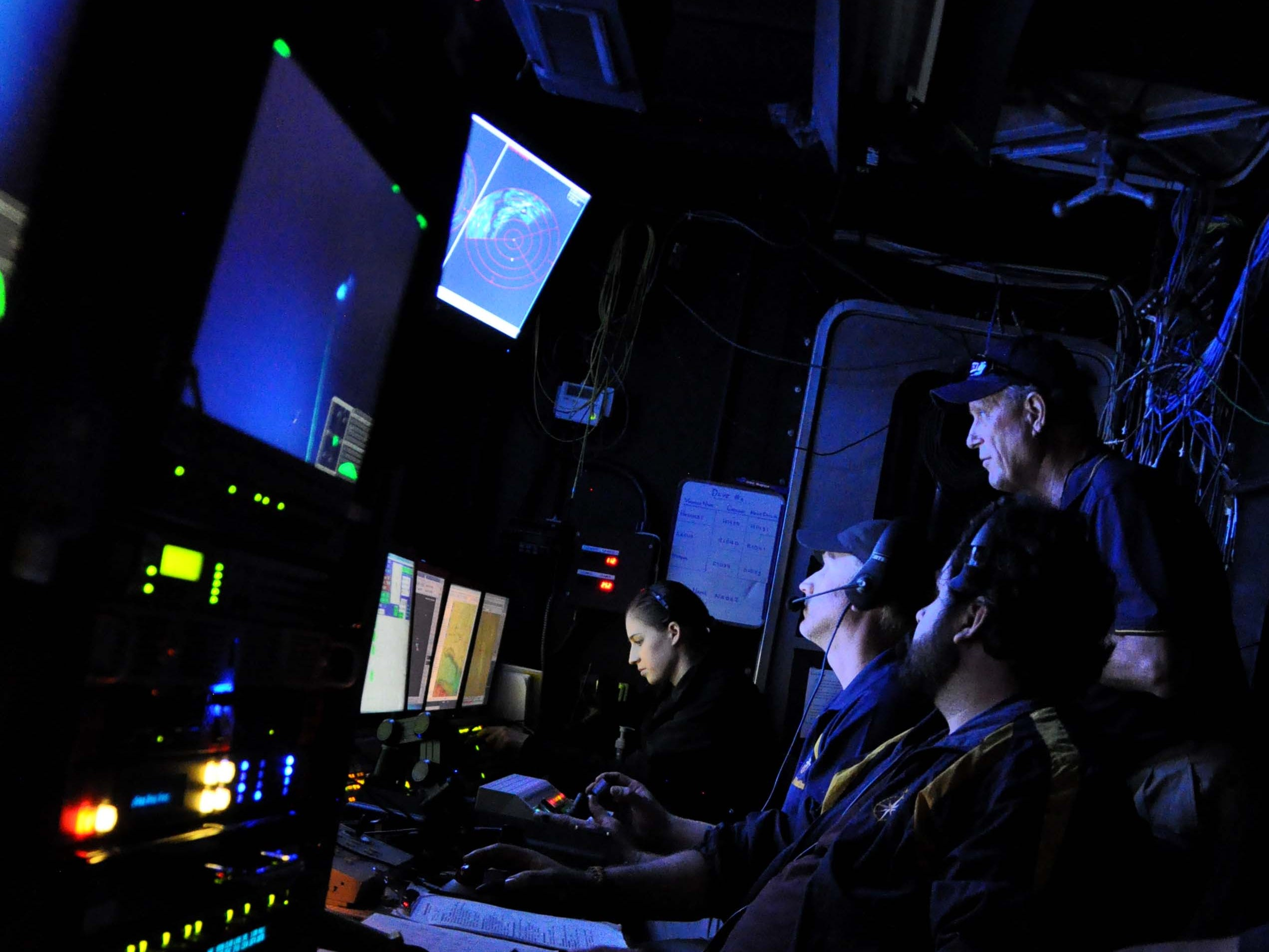 Melissa Baffa's view from her station in the control van, where the watch team conducts exploration. Looking down the line, the ROV pilots and navigator are visible, with Dr. Robert Ballard standing behind them. This 2015 photo shows Ballard's first return to the hydrothermal vents he discovered, 38 years later.