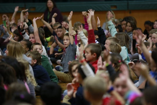 Weston Elementary students raise their hands Monday to be called upon by former Michigan State basketball player Anthony Ianni.