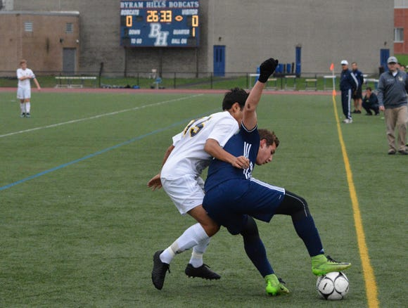 Byram Hills forward Spencer Weinhoff keeps the ball in against Pelham defender Philip Dulock Monday.