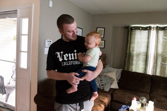 Andrew Morrison holds his son Dominic at his home in Newark. Morrison receives vivitrol to help stay off drugs and live a normal life.