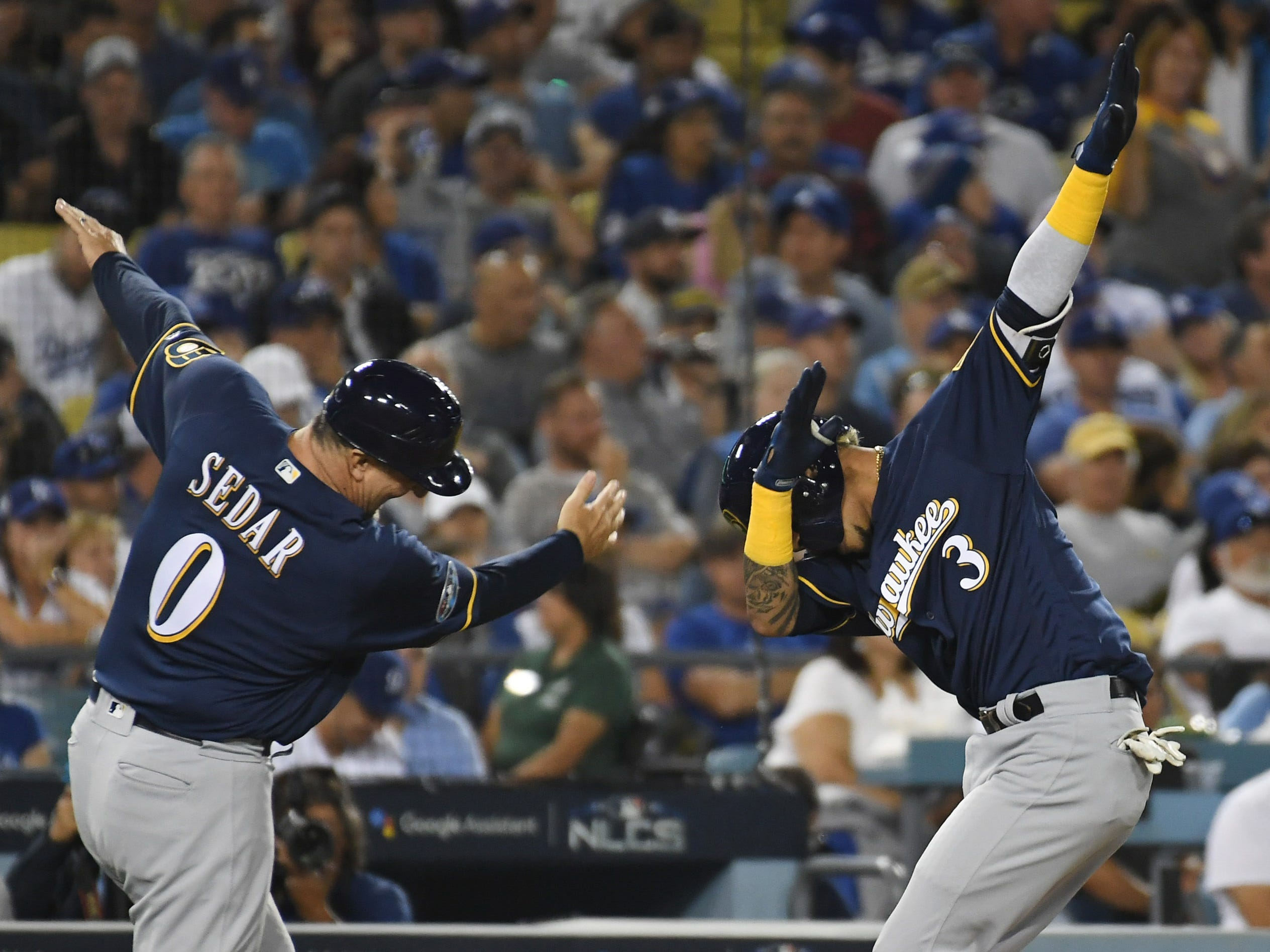 NLCS Game 3: Brewers shortstop Orlando Arcia celebrates with third base coach Ed Sedar after hitting a two-run homer in the seventh inning.
