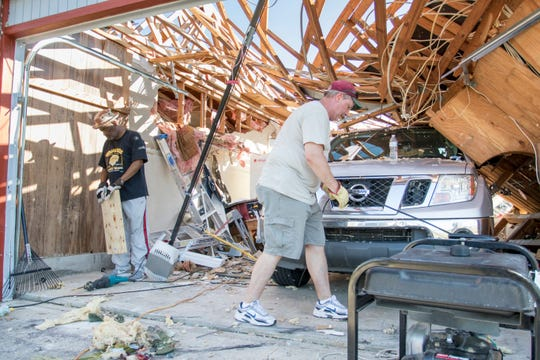 Donald Howell helps Rick Gaddy remove debris from his garage after Hurricane Michael in Panama City, Florida on Monday, October 15, 2018. (Via OlyDrop)