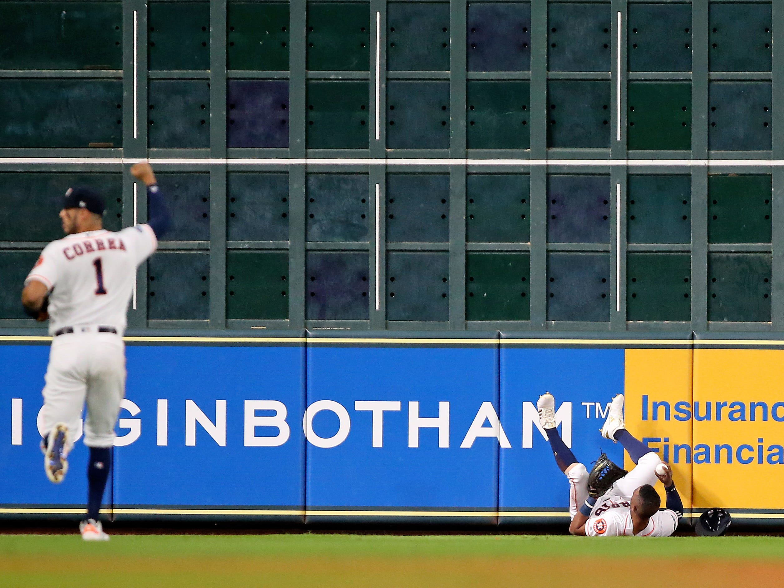 ALCS Game 3: Astros shortstop Carlos Correa signals a catch by left fielder Tony Kemp in the third inning.