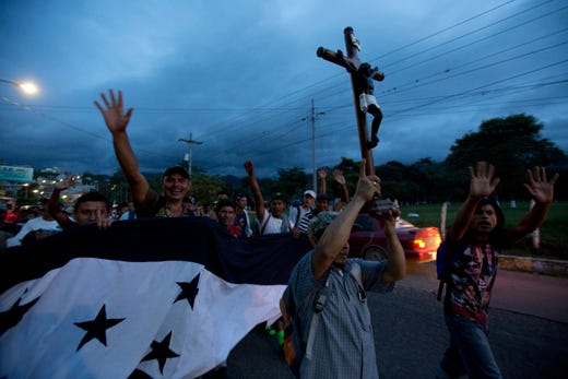 A Honduran migrant holds up a replica of the Black Christ of Esquipulas as a caravan of migrants making their way to the U.S. arrives to Esquipulas, Guatemala, Monday, Oct. 15, 2018. The Guatemalan police blocked the road of the caravan for several hours before allowing the migrants to continue on their way. (AP Photo/Moises Castillo) ORG XMIT: XMC137