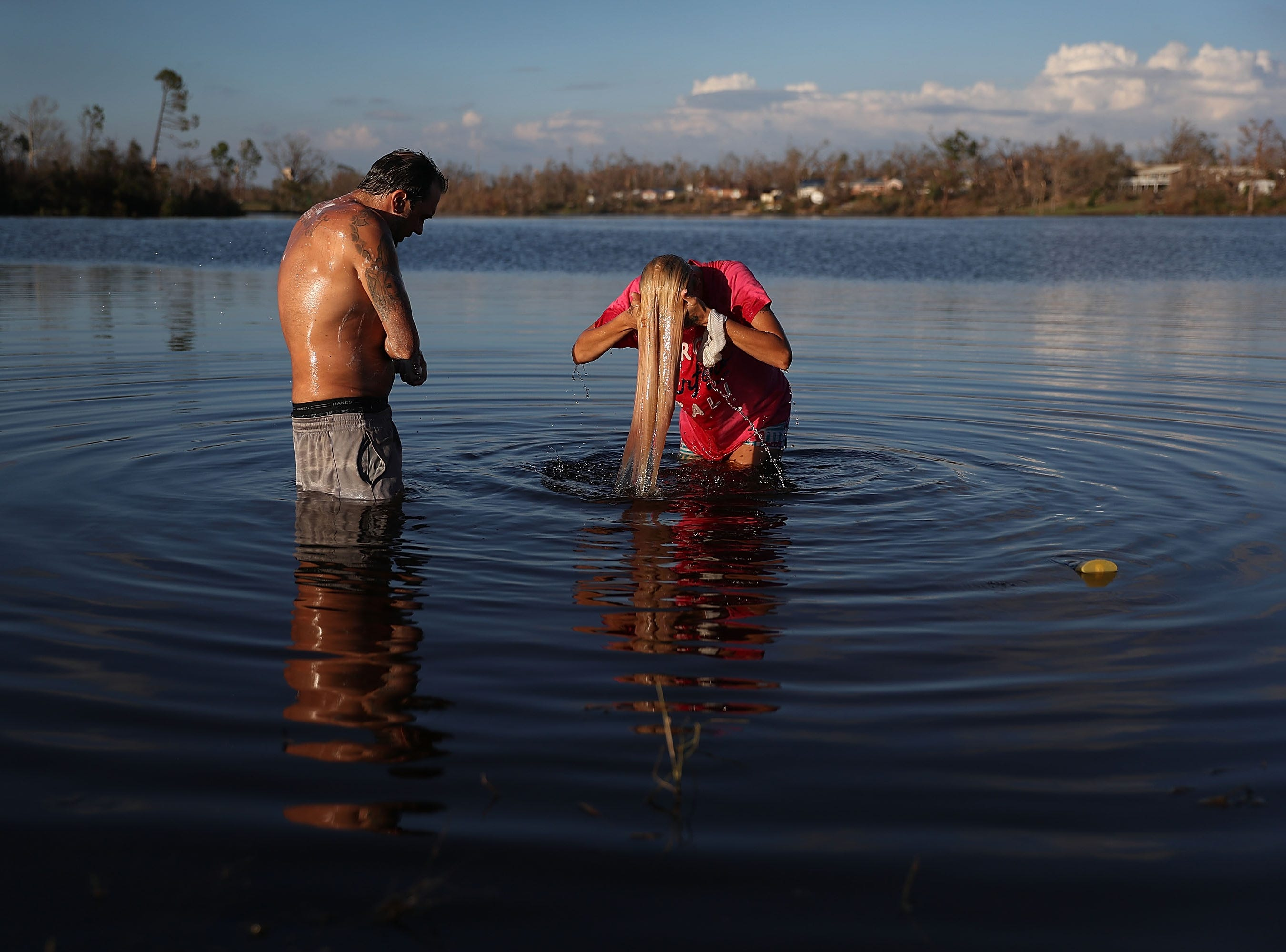 Justin Norman and Lisa Salle wash themselves in Lake Martin because their home has no running water after much of the municipality's infrastructure was damaged by Hurricane Michael on Oct. 16, 2018 in Panama City, Fla. Michael slammed into the Florida Panhandle on October 10 as a Category 4 storm, causing widespread damage and claiming as many as 26 lives.