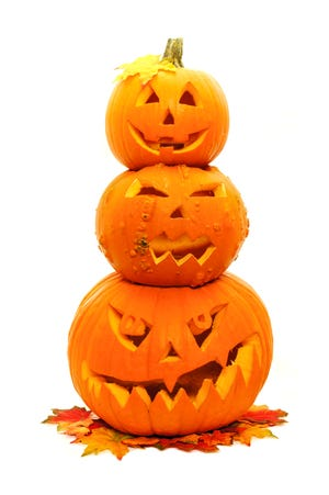 Group of three stacked Jack o Lanterns with autumn leaves