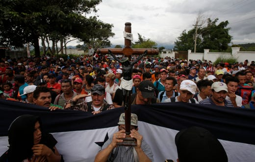 A Honduran migrant holds up a replica of the Black Christ of Esquipulas as Guatemalan police temporarily block the road after the caravan crossed the Honduras-Guatemala border without incident, in Esquipulas, Guatemala, Monday, Oct. 15, 2018. The caravan began as about 160 people who first gathered early Friday to depart from San Pedro Sula, figuring that traveling as a group would make them less vulnerable to robbery, assault and other dangers common on the migratory path through Central America and Mexico. The group has since grown to at least 1,600 people. (AP Photo/Moises Castillo) ORG XMIT: XMC127