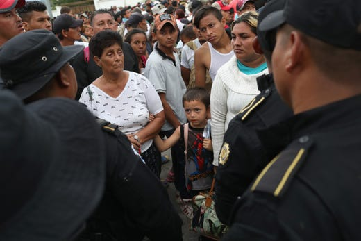 ESQUIPULAS, GUATEMALA - OCTOBER 15:  A caravan of more than 1,500 Honduran migrants pauses at a Guatemalan police checkpoint after crossing the border from Honduras on October 15, 2018 in Esquipulas, Guatemala. The caravan, the second of 2018, began Friday in San Pedro Sula, Honduras with plans to march north through Guatemala and Mexico en route to the United States. Honduras has some of the highest crime and poverty rates in Latin America.  (Photo by John Moore/Getty Images) ORG XMIT: 775243532 ORIG FILE ID: 1052219362