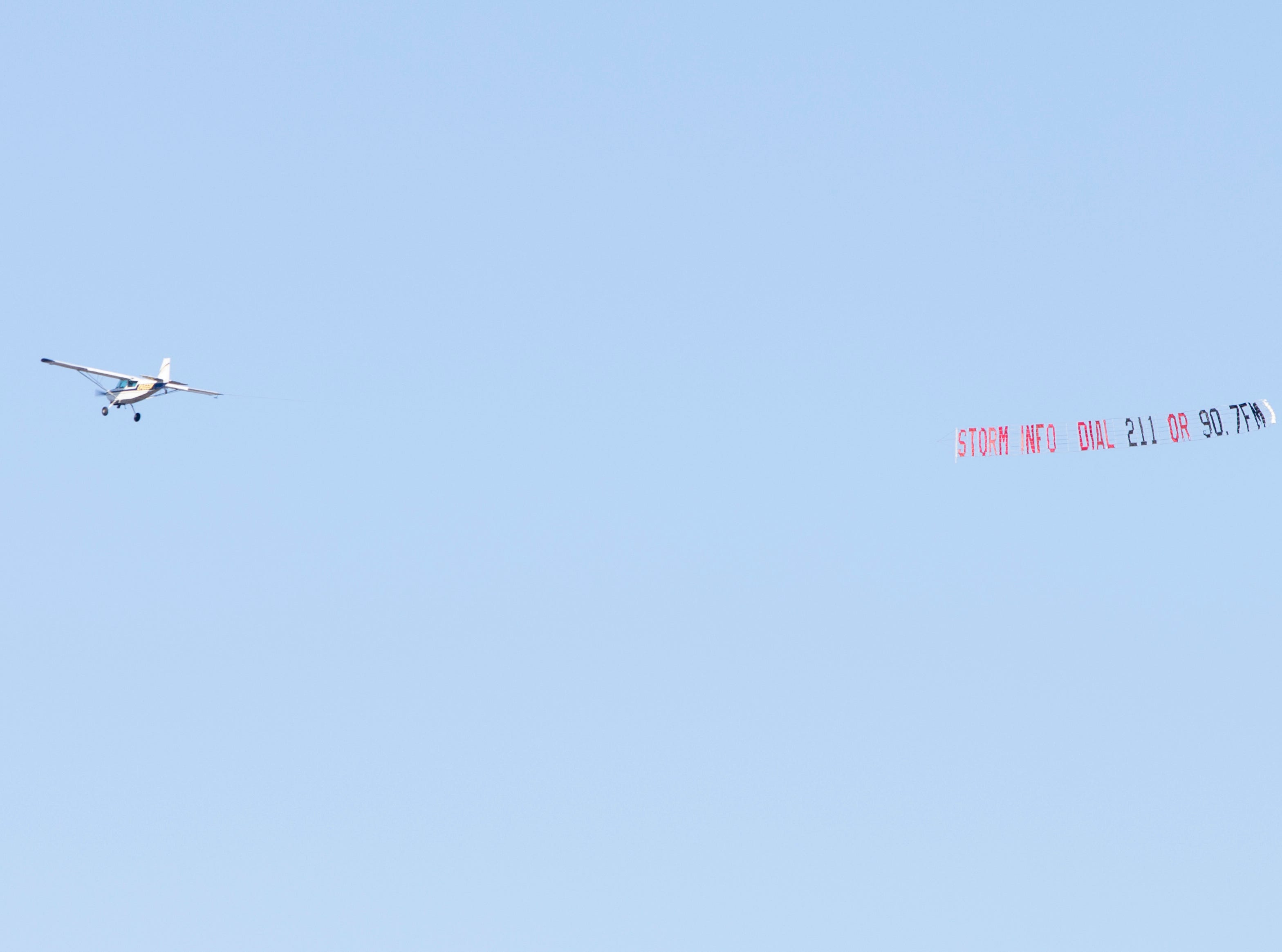 A plane flies over neighbors with a banner letting people know where to get storm information after Hurricane Michael in Panama City, Florida on Monday, October 15, 2018. (Via OlyDrop)